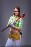 Kvinnlig arbetare i overaller som rymmer en yxa Royaltyfria Bilder