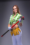 Kvinnlig arbetare i overaller som rymmer en yxa Fotografering för Bildbyråer