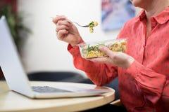 Kvinnlig arbetare i regeringsställning som har sund pastalunch på skrivbordet royaltyfri fotografi