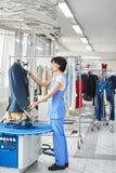 Kvinnlig arbetare i tvätteriservice processen av att arbeta på universell automatisk utrustning för att ånga, att stryka och att  arkivbild