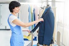 Kvinnlig arbetare i tvätteriservice processen av att arbeta på universell automatisk utrustning för att ånga, att stryka och att  royaltyfri bild