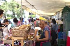 Kvinnlig arbetare på bagerit som säljer bröd arkivfoto