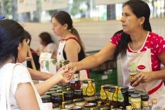 Kvinnlig arbetare på gatamarknaden som ger en honungprövkopia på 'bioferiaen ', royaltyfri bild