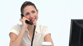 Kvinnlig arbetare på telefonen på hennes skrivbord Royaltyfria Bilder