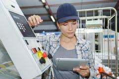 Kvinnlig arbetare som använder den digitala minnestavlan i fabriks- bransch arkivfoton