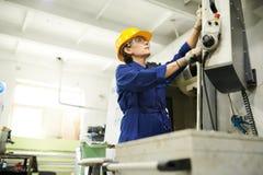 Kvinnlig arbetare som använder maskinenheter arkivfoton