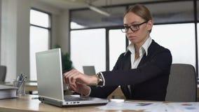 Kvinnlig arbetare som kontrollerar tid på klockan som snabbt skriver för att avsluta rapporten, stopptid stock video
