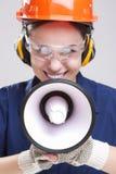 Kvinnlig arbetare som poserar med megafonen och den bärande hardhaten för skydd Vertikal bildsammansättning Royaltyfri Bild