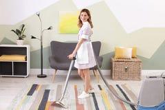 Kvinnlig arbetare som tar bort smuts från matta med yrkesmässig dammsugare, inomhus fotografering för bildbyråer