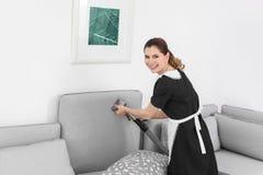 Kvinnlig arbetare som tar bort smuts från soffan med yrkesmässig dammsugare, inomhus royaltyfri fotografi