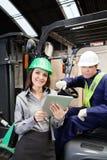 Kvinnlig arbetsledare- och gaffeltruckchaufför With Digital Arkivbilder