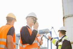 Kvinnlig arbetsledare som använder walkie-talkie medan arbetare som diskuterar i bakgrund på skeppsvarven fotografering för bildbyråer