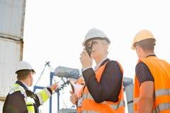 Kvinnlig arbetsledare som använder walkie-talkie medan arbetare som diskuterar i bakgrund på skeppsvarven arkivbild