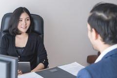 Kvinnlig arbetsledare som intervjuar en ny manlig personal arkivbild