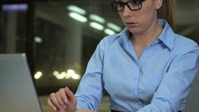 Kvinnlig arbetsnarkoman som gäspar skriva bärbar datortangentbordet som sent arbetar - natt, stopptid arkivfilmer
