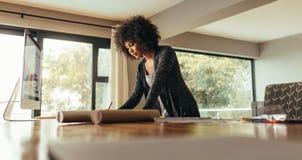 Kvinnlig arkitekt som arbetar det hemmastadda kontoret royaltyfria foton
