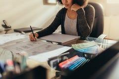 Kvinnlig arkitekt som arbetar nya designer på henne arbetsskrivbord royaltyfri fotografi