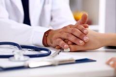 Kvinnlig arm för vänlig manlig doktorshåll i regeringsställning arkivfoton
