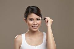 Kvinnlig asiatisk applicerande mascara Royaltyfri Fotografi