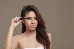 Kvinnlig asiatisk applicerande mascara Royaltyfri Foto