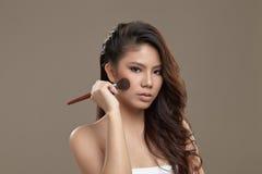 Kvinnlig asiatisk applicerande rouge Fotografering för Bildbyråer