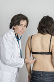 Kvinnlig auscultating ung patient för doktor vid stetoskopet Royaltyfria Bilder