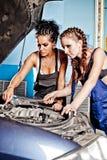 Kvinnlig auto mekaniker som två reparerar en bil arkivfoton