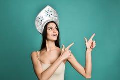 Kvinnlig bärande för lockhatten för ryss traditionell kokoshnik, visar dess läge åt sidan över tomt kopieringsutrymme royaltyfri fotografi