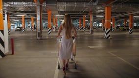 Kvinnlig bärande shoppa vagn till och med parkering stock video