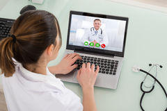 Kvinnlig bärbar dator för doktor Video Chatting On Fotografering för Bildbyråer