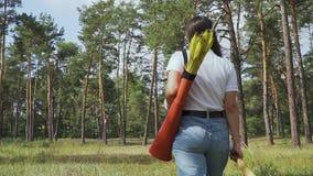 Kvinnlig bågskytt som går till och med skogen stock video