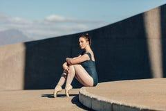 Kvinnlig balettdansör som behagfullt sitter, medan vila hennes tånolla arkivfoton