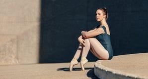 Kvinnlig balettdansör som behagfullt sitter, medan vila hennes tånolla royaltyfri fotografi