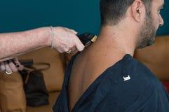 Kvinnlig barberare som arbetar med hårclipperen som rakar ung mans hals Royaltyfri Fotografi