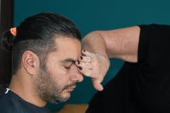 Kvinnlig barberare som gör ren ung mans framsida med hennes hand, når att ha rakat hans hår royaltyfri bild