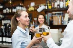 Kvinnlig barista och två klienter Arkivbild