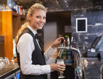 Kvinnlig bartender som drar ett exponeringsglas av öl, medan se kameran Arkivfoton