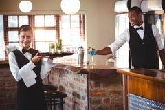 Kvinnlig bartender som rymmer ett portionmagasin med två coctailexponeringsglas arkivfoton