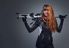 Kvinnlig Biathlonm?stare f?r r?dh?rig man som siktar med ett konkurrenskraftigt vapen arkivbilder