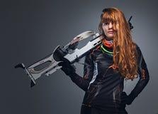 Kvinnlig Biathlonm?stare f?r r?dh?rig man som siktar med ett konkurrenskraftigt vapen royaltyfri fotografi