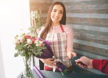 Kvinnlig blomsterhandlare på arbete: modern bukett för nätt ungt brunettdanandemode av olika blommor Arbeta för kvinnor royaltyfri fotografi