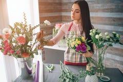 Kvinnlig blomsterhandlare på arbete: modern bukett för nätt ungt brunettdanandemode av olika blommor Arbeta för kvinnor royaltyfri foto