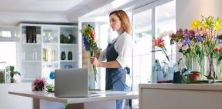 Kvinnlig blomsterhandlare på arbete som skapar en bukett royaltyfri foto