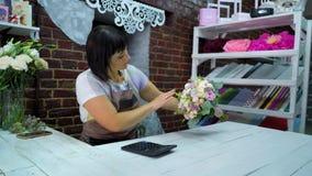 Kvinnlig blomsterhandlare som räknar kostnad av buketten med räknemaskinen i en blomsterhandel stock video