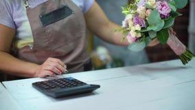 Kvinnlig blomsterhandlare som räknar kostnad av buketten med räknemaskinen i en blomsterhandelcloseup lager videofilmer