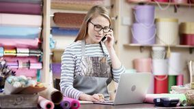Kvinnlig blomsterhandlare som talar på mobiltelefonen, medan genom att använda bärbara datorn i blomsterhandeln, kontrollbeställn lager videofilmer