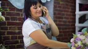 Kvinnlig blomsterhandlare som talar på telefonen som diskuterar kostnad av buketten med kunden i en blomsterhandel arkivfilmer