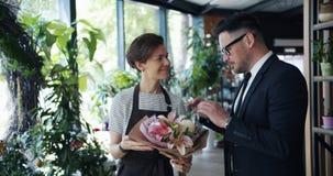 Kvinnlig blomsterhandlare som talar till den manliga kundinnehavgruppen av blommor i lager stock video