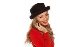 Kvinnlig blond användande mobil Arkivfoto