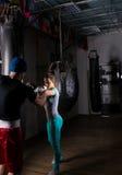 Kvinnlig boxare i boxninghandskar som utbildar med hennes soffa och boxas Arkivfoton